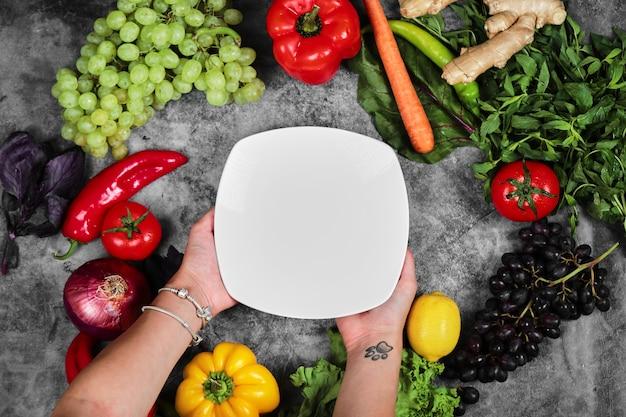 Vrouw met witte plaat op marmeren achtergrond met verse groenten. Gratis Foto