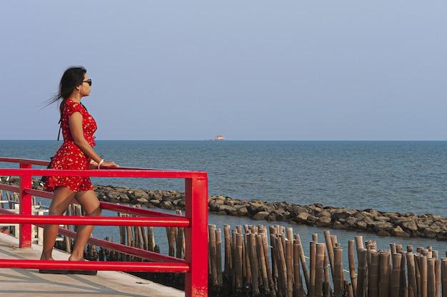Vrouw met zonnebril en een rode jurk staande op de red boardwalk-brug in thailand Gratis Foto
