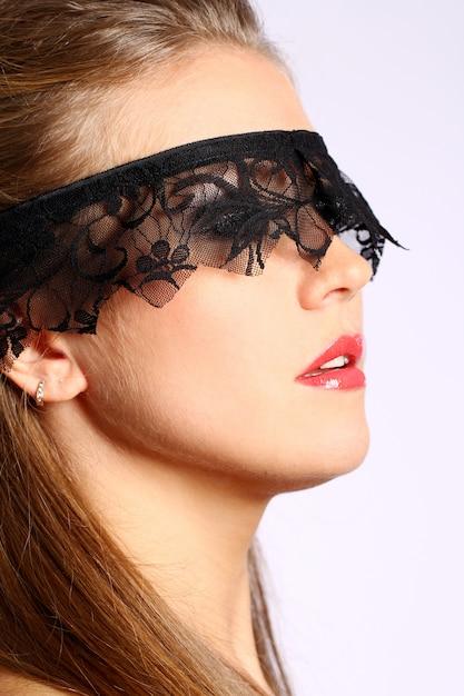 Vrouw met zwart kantmasker over haar gezicht Gratis Foto