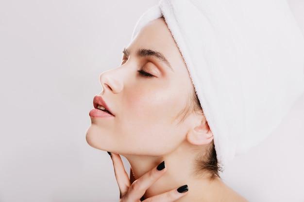 Vrouw met zwarte manicure masseert zachtjes nek. portret van een jong meisje na douche op witte muur. Gratis Foto
