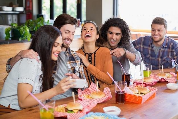 Vrouw mobiel tonen aan vrolijke vrienden in restaurant Premium Foto