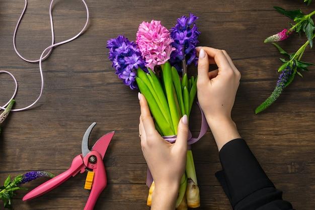Vrouw mode modern boeket van verschillende bloemen maken op houten oppervlak Gratis Foto