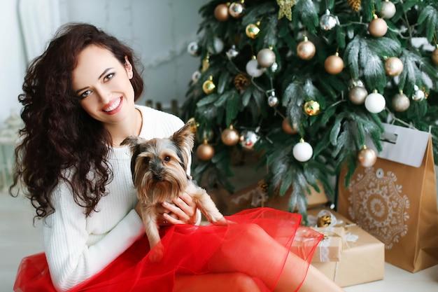Vrouw model in een rode jurk in een fotostudio met een nieuwjaarsgeschenk in haar handen. Premium Foto