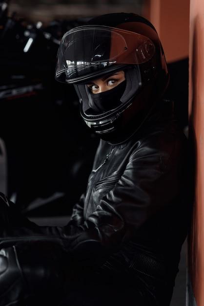 Vrouw motorrijder haar enduro motor of chopper rijden gekleed in stijlvolle lederen kleding en beschermende uitrusting Premium Foto