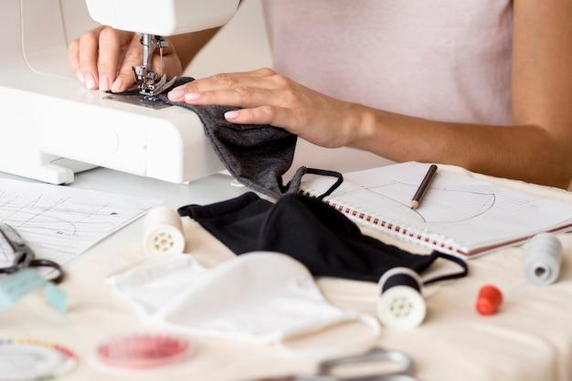 Vrouw naaien gezichtsmasker met laptop Gratis Foto