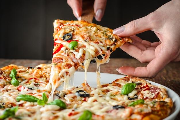 Vrouw neemt een stuk pizza Premium Foto