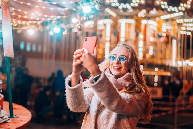 Vrouw neemt selfie op defocus achtergrondlicht in avondstraat Gratis Foto