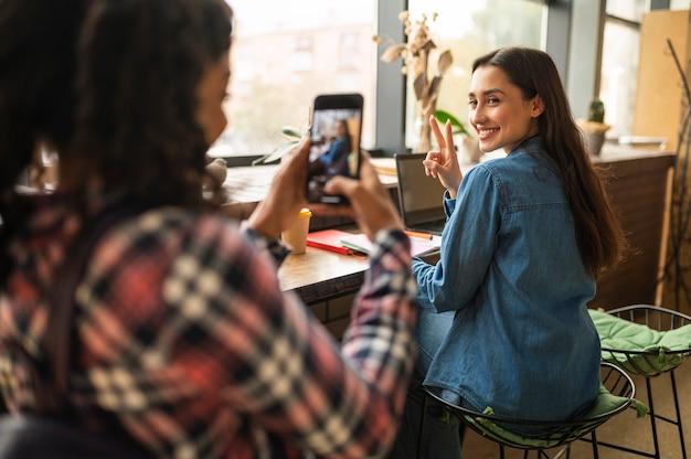 Vrouw nemen foto van haar vriend in een café Gratis Foto