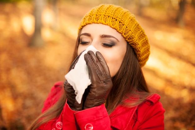 Vrouw niezen in zakdoek in de herfst Gratis Foto