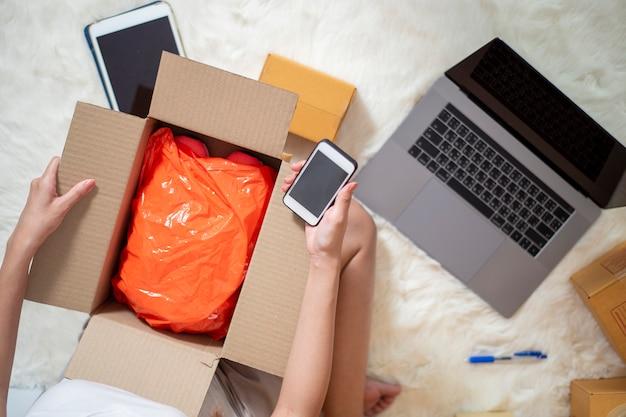 Vrouw ondernemer eigenaar mkb-bedrijf controleert de bestelling met smartphone, laptop en verpakking om haar klant te sturen Premium Foto