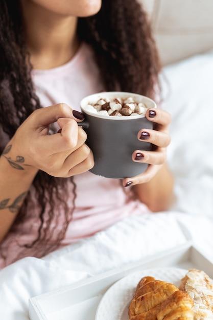 Vrouw ontbijten op bed in een licht hotelappartement of thuis. venster licht portret jong meisje croissant eten en koffie drinken. Premium Foto