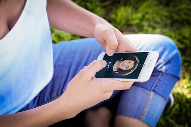Vrouw ontgrendelen smartphone met gezichtsherkenningstechnologie Premium Foto
