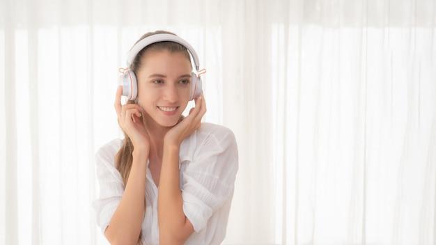 Vrouw ontspannen die aan muziek met hoofdtelefoons luistert. Premium Foto