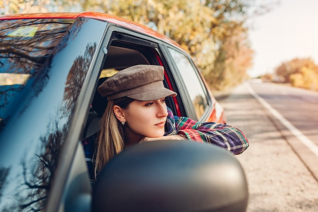 Vrouw ontspannen in auto. bestuurder die uit autimobiel venster op de herfstweg kijkt. Premium Foto