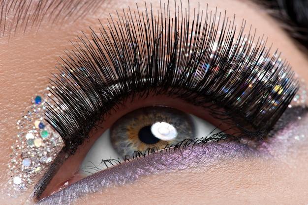 Vrouw oog met lange zwarte valse wimpers en creatieve mode lichte make-up Gratis Foto