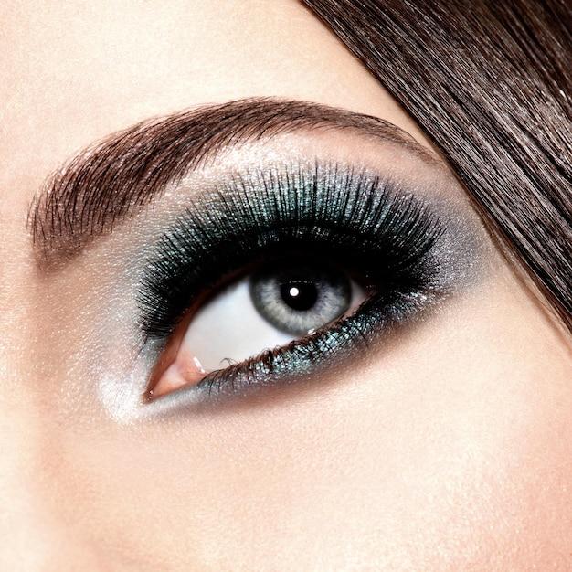 Vrouw oog met turquoise make-up. lange valse wimpers. macro-opname Gratis Foto