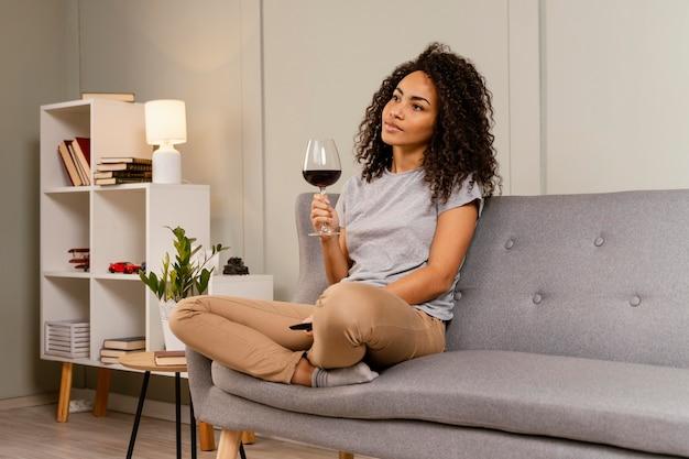Vrouw op bank tv kijken en wijn drinken Gratis Foto