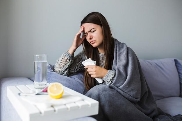 Vrouw op de bank met medicatie Gratis Foto