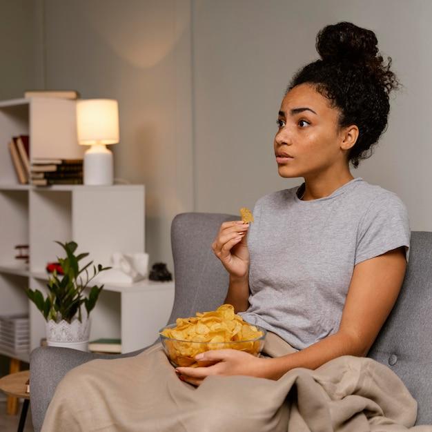 Vrouw op de bank tv kijken en chips eten Gratis Foto