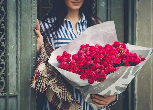 Vrouw op de deur met een groot roze bloemboeket Gratis Foto