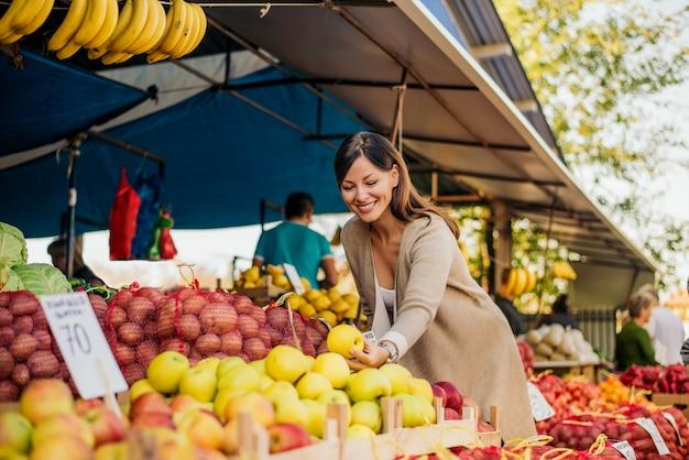 Vrouw op de markt, op zoek naar groenten en fruit. Premium Foto