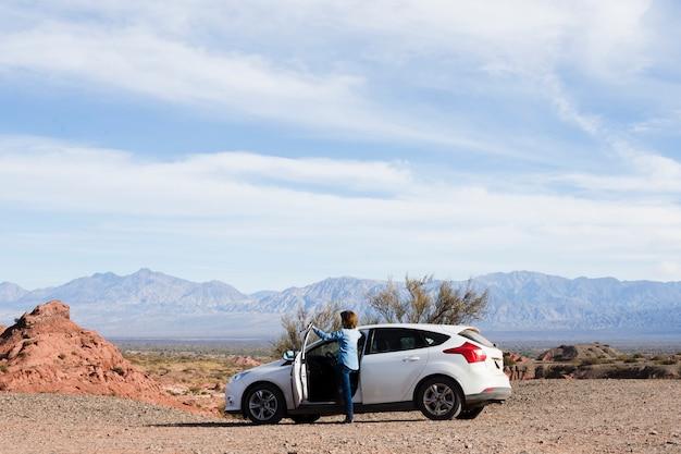 Vrouw op de weg die van het landschap geniet Gratis Foto
