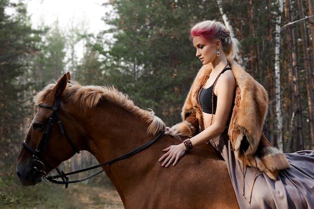 Vrouw op een paard in de herfst. Premium Foto