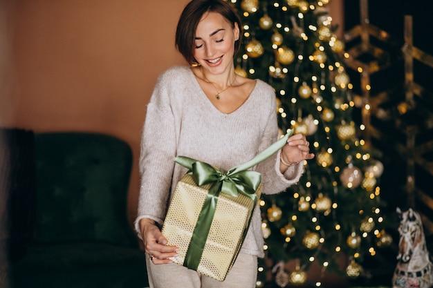 Vrouw op kerstmis die kerstmis huidig houdt door de kerstmisboom Gratis Foto