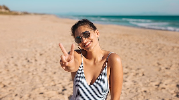 Vrouw op strand dat v zucht maakt Gratis Foto