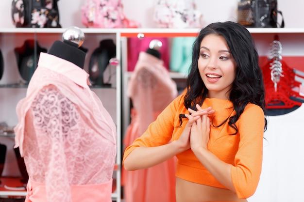 Vrouw opgewonden te kijken naar een roze jurk Gratis Foto