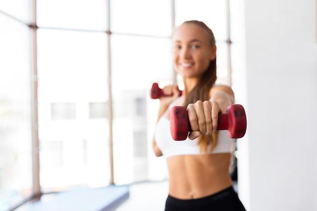 Vrouw opleiding met gewichten in gymnastiek Gratis Foto