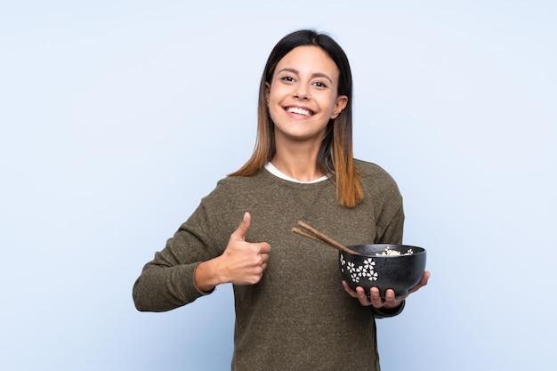 Vrouw over blauwe muur met duimen omhoog terwijl een kom noedels met stokjes Premium Foto