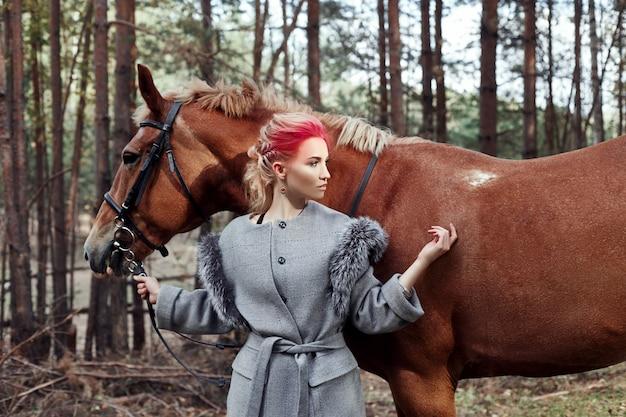 Vrouw paard in de herfst. creatieve felroze make-up Premium Foto