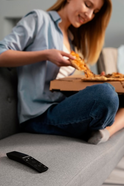 Vrouw pizza eten tijdens het kijken naar tv close-up Gratis Foto