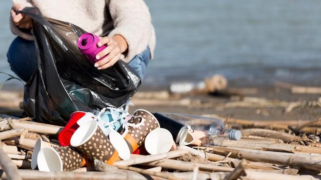 Vrouw plukken afval van zee Gratis Foto