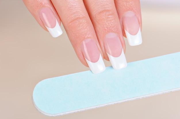 Vrouw polijsten vingernagels bij de hand met nailfile Gratis Foto
