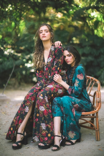 Vrouw poseren in gebloemde jurken en hoge hakken Gratis Foto