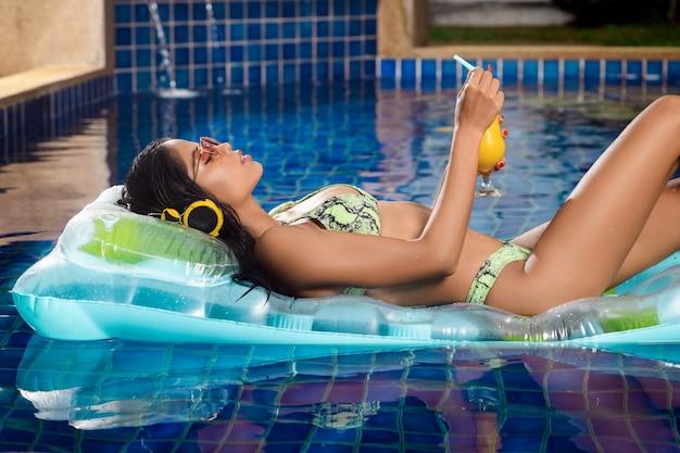 Vrouw poseren liggend op een drijvende matras Premium Foto