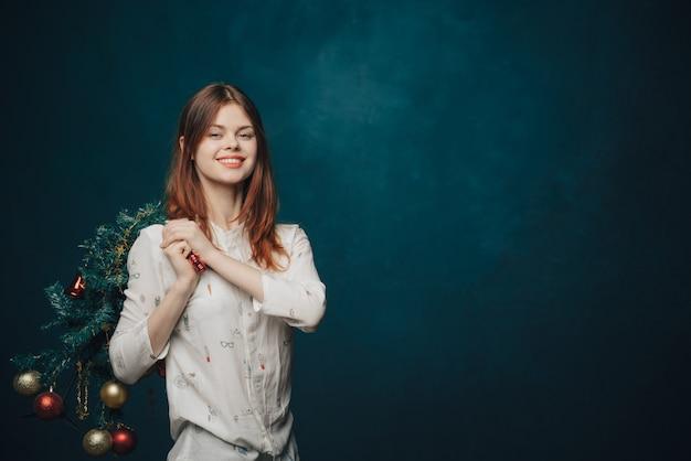 Vrouw poseren met kerstboom Premium Foto