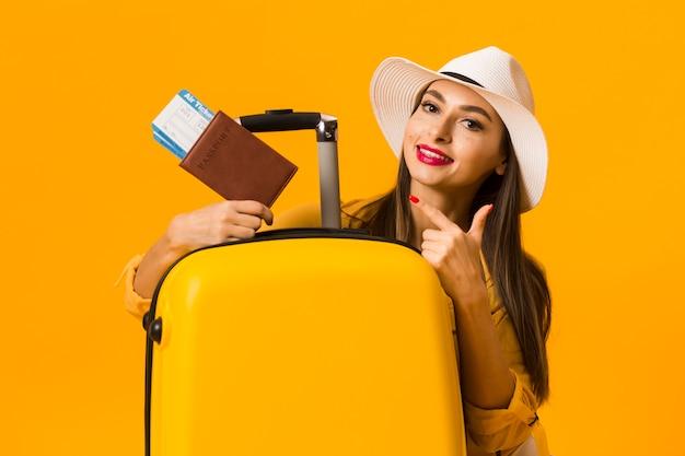 Vrouw poseren naast bagage en wijzend op reizen essentials Gratis Foto