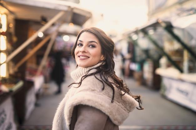 Vrouw poseren terwijl ze op straat staat. kerst vakantie concept. Premium Foto