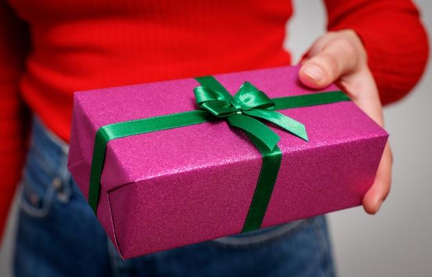 Vrouw presenteert een cadeau voor kerstmis in een heldere geschenkdoos. detailopname. Premium Foto