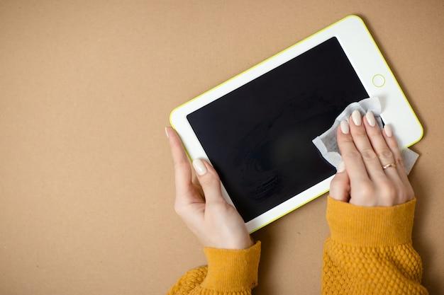 Vrouw reinigt witte tablet, gadget desinfectie terwijl virus. thuiskantoor terwijl u zelf isoleert, thuiswerkend. online onderwijs, e-learning tijdens quarantaine. Premium Foto