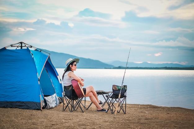 Vrouw reiziger kamperen en vissen in de buurt van het meer op vakantie. Premium Foto