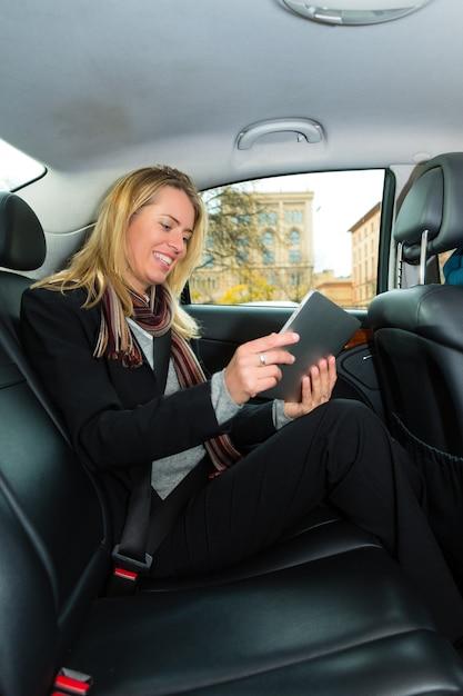 Vrouw rijden in taxi met behulp van tablet pc Premium Foto