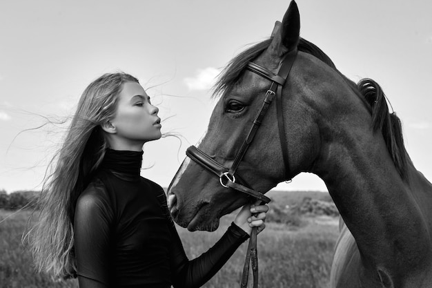 Vrouw rijder staat naast het paard in het veld. mode portret van een vrouw en de merries zijn paarden in het dorp in het gras. blondevrouw die een paard houden Premium Foto