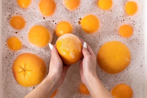 Vrouw rijp sinaasappel wassen, grapefruit onder kraan in de gootsteen keuken, fruit weken in zeepachtig water grondig wast na opslag Premium Foto