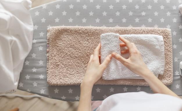 Vrouw rollen gestreken schone handdoeken permanent op strijkplank Premium Foto