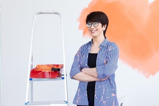 Vrouw schildert de muur Premium Foto