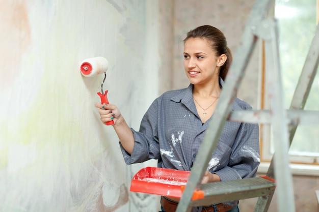 Vrouw schildert muur met rol thuis Gratis Foto